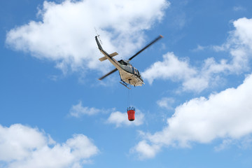 Firefighter helicopter flying with bambi bucket.
