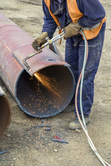 Worker cutting metal with flame torch