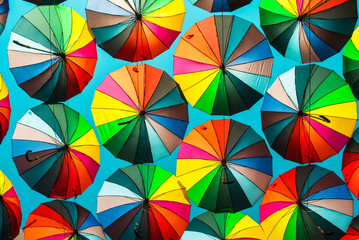 Colorful umbrella with colors of rainbow in the blue clear sky. Conceptual bright background.