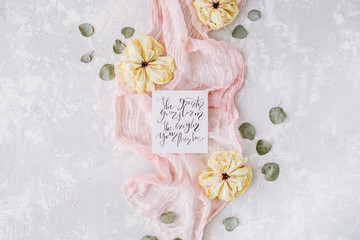 "inspirational quote ""the greater your storm the brighter your rainbow"" written in calligraphy style on paper with dry white tulips, eucalyptus petals and pink textile on concrete background. Flat lay"