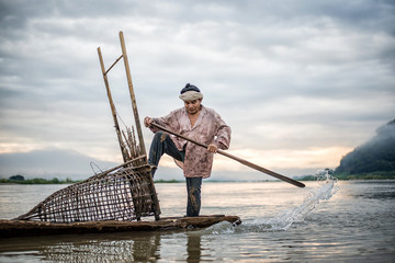 Fisherman on boat in action when fishing of fish trap on Mekong
