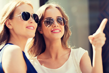 happy women in sunglasses pointing finger outdoors