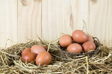 Fresh chicken eggs in the straw nest on wooden vintage backgroun