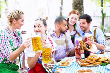Freunde trinken Bier im Biergarten
