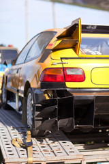 Rearlights of yellow sport car with black diffuser