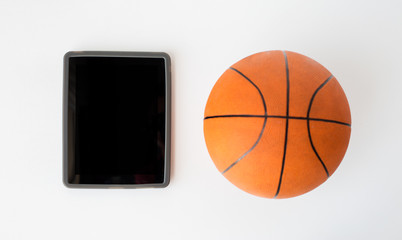 close up of basketball ball and tablet pc computer