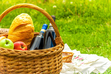 Picnic basket with wine,fruits and bread with sunny, green and grassy background