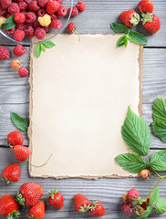 Healthy eating concept. Old paper with fresh strawberries and raspberries on wooden table. Copy space, top view, high resolution product.