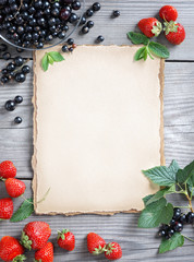 Healthy food background. Old paper with Strawberry and Currant on wooden table. Copy space, top view, high resolution product. Harvest concept.