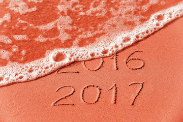 2016 2017 inscription written on wet red beach sand is washed away by sea wave