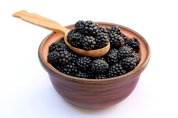 Juicy ripe blackberries in a bowl with spoon isolated
