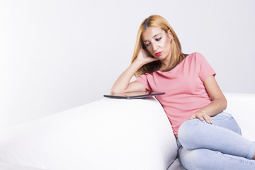 Young woman sitting on a white couch using her tablet pc, bored beyond belief.