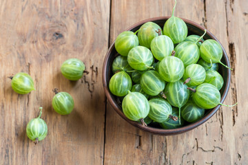 Fresh green gooseberries in bowl on table close-up