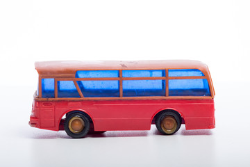 Model of a red bus with blue windshield on white background