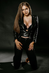 beautiful sexy brunette girl with long hair and big boobs. in the studio on a black background. Dressed in black jeans black leather jackets. girl in the image of rocker and biker. Advertising Space