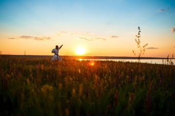 Silhouette of sportive man training karate in field at sunrise.