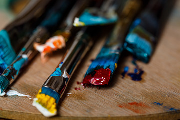 Close up of oil paints and brushes on palette.
