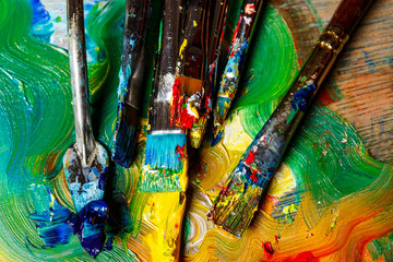 Close up of oil paints and brushes on palette. Above.