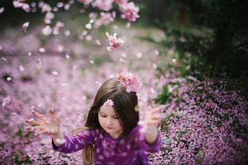 Young girl throwing cherry blossom into air