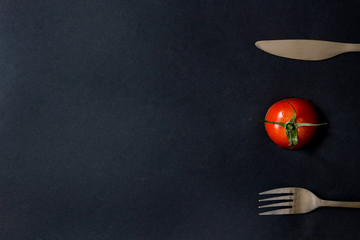 Tomato and cutlery on the table