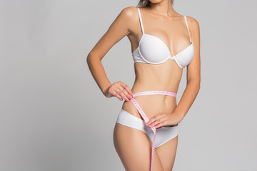 Woman measuring her slim body on gray background, in white lingerie or underwear
