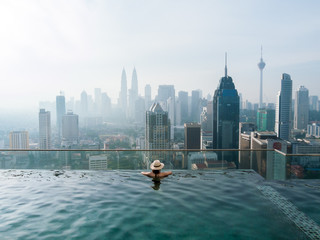 Woman enjoying the view from an infinity pool