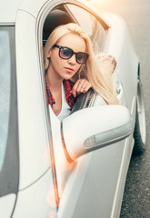 Young woman in sunglasses look out from the car window