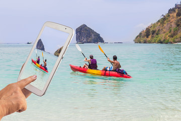 Couple paddling kayak in the andaman sea during her friend using digital tablet taking photo