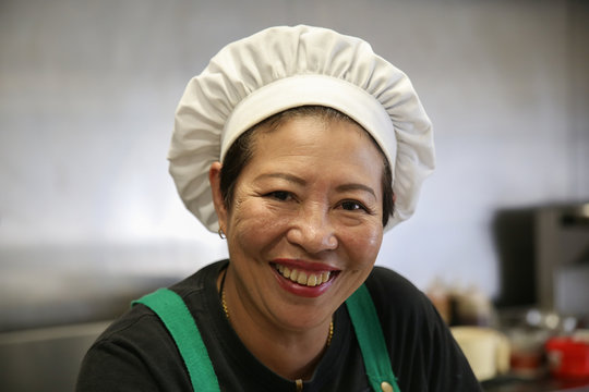 Smiling Asian woman chef portrait in professional restaurant kitchen