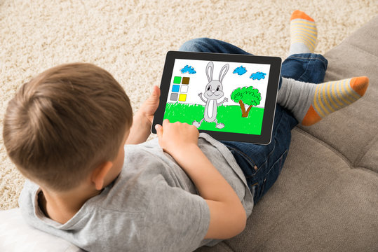 Cute Little Child Playing Game On Digital Tablet