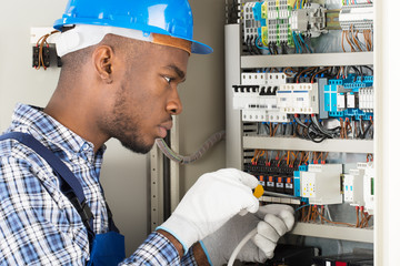 Technician Repairing Fusebox With Screwdriver
