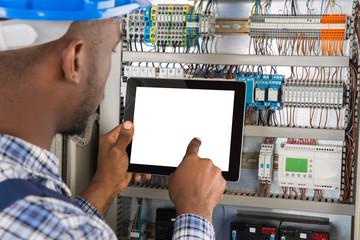 Technician Using Digital Tablet While Examining Fusebox