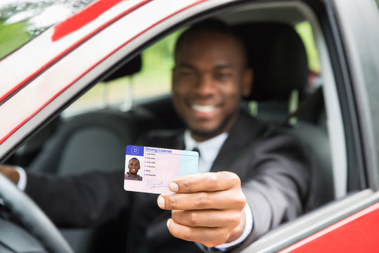 Businessman Showing His Driving License From Open Car Window