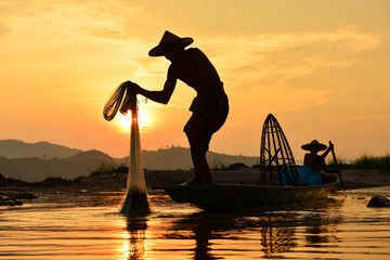 The suluate  fisherman casting a net into the water during on  sunset,Nongkhai Thailand