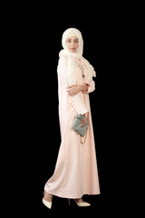 Studio photo of the girl of Middle Eastern appearance in the bright, closed, modern Muslim dress, high heels, on a black background