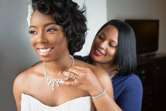 Mother helping her daughter get dressed for her wedding. Bride.