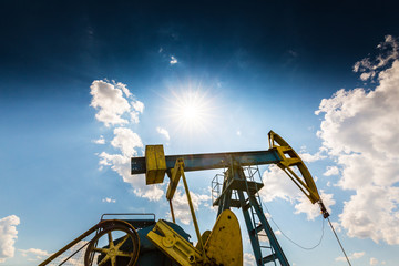 Oil field with old pump jack, profiled on blue sky with white clouds, on a bright day