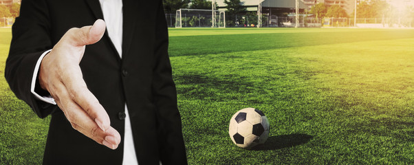 A man in suit extending hand to handshake with soccer ball at soccer field