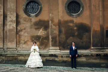 Newlyweds stand apart under the round windows of an old cathedra