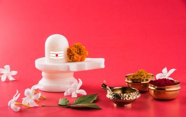 Shiva Linga made up of white marble decorated with flowers & bael leaf known as Aegle marmelos, over white background, maha shiva ratri a festival of hindu God shankar or shankar bhagwan or bholenath