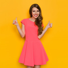 Smiling Woman In Pink Dress Showing Thumbs Up