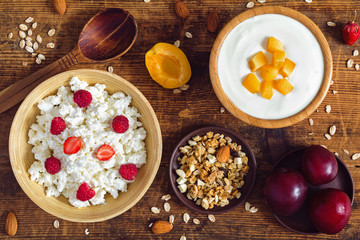 Cottage cheese with raspberries, plain greek yogurt with peaches, homemade crunchy granola, almonds and red plums on rustic wooden table. Top view food