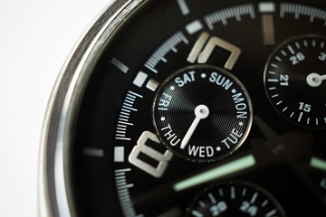 Macro detail of a silver and black watch with the focus on the rounded week calender displaying the days in week as a symbol of planning and precision