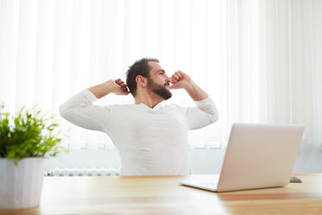 Man stretching his back at desk