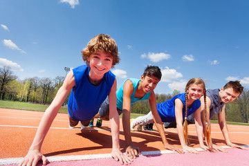 Happy teenagers holding plank outdoor on the track