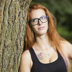 young red haired woman student relaxing learning in park sunny weather