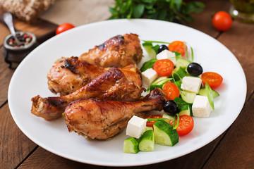 Appetizing oven baked golden chicken drumsticks and Greek salad