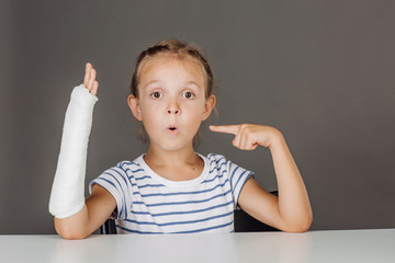 Young surprised girl with broken arm is sitting at the table.