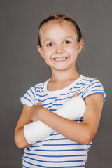 Happy smiling girl with broken arm is standing on the gray background