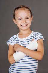 Happy smiling girl with broken arm is standing on the gray background.